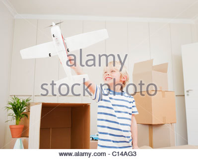 Jungen spielen mit Modellflugzeug im neuen Haus - Stockfoto