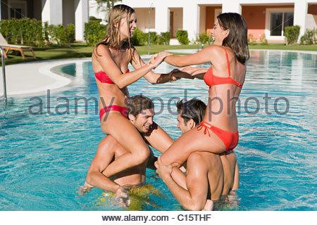 Vier Freunde im Schwimmbad, im Urlaub, Frauen auf Männer Schultern - Stockfoto