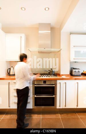 Indische Asiatin in eine stilvolle, moderne Küche mit weißen Einheiten und eine hölzerne Arbeitsplatte - Stockfoto
