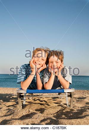 Zwei Jungs (7-9) auf Liegestuhl liegend - Stockfoto