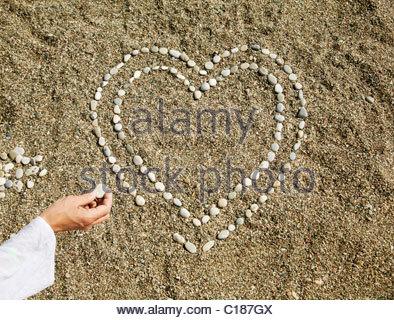 Kieselsteine in Herzform auf sand - Stockfoto