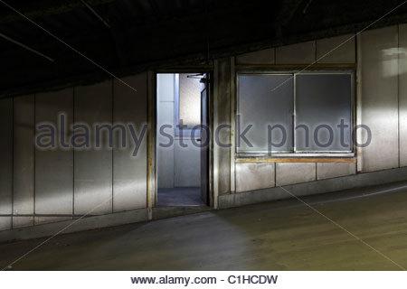 Schlupftür in einem Parkhaus mit Scheinwerfern aus dem Auto - Stockfoto