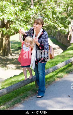 Mutter Mitarbeitende Tochter gehen auf Geländer im zoo - Stockfoto