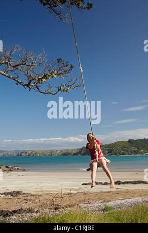 Mädchen auf Seil schwingen, Oakura Bay, Northland, Nordinsel, Neuseeland - Stockfoto