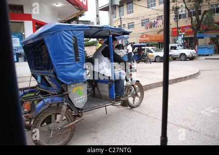 Ein Mann fährt seine Mototaxi in einer geschäftigen Stadt in Südamerika - Stockfoto