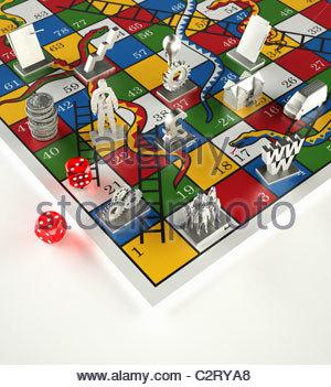 Token und Würfel auf Snakes And Ladders Spiel - Stockfoto