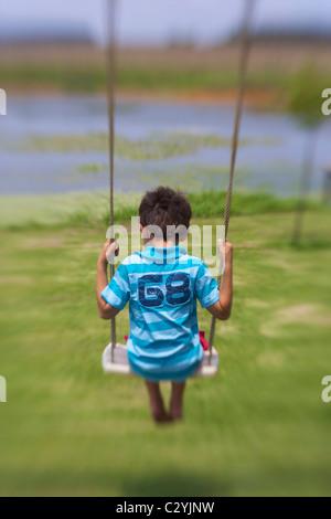 Rückansicht eines kleinen Jungen auf einer Schaukel, Paulpetersburg, Kwazulu-Natal, Südafrika - Stockfoto
