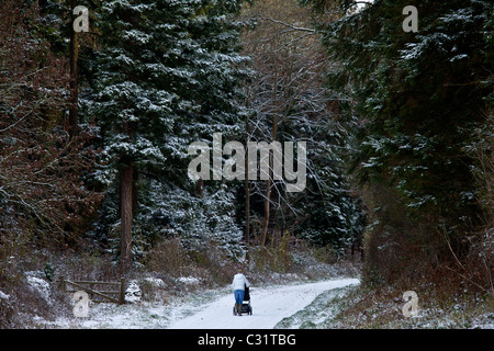 Mutter mit Kind im Kinderwagen an verschneiten Tag in Cotswolds, UK - Stockfoto