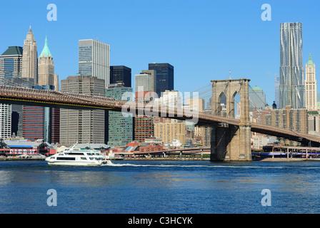 Eine Flusskreuzfahrt Schiff auf den East River Überschrift unter der Brooklyn Bridge in New York City. - Stockfoto