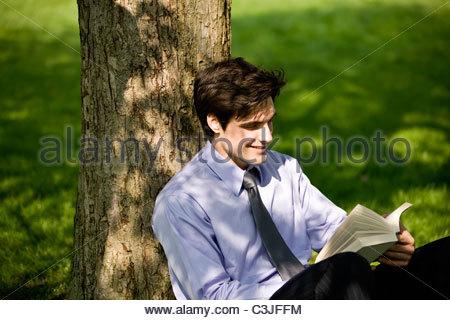 Ein Geschäftsmann an einen Baum gelehnt, ein Buch zu lesen - Stockfoto
