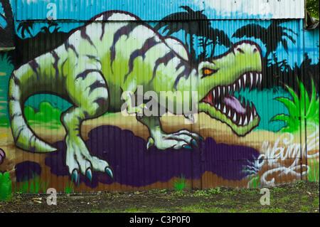 Graffiti auf eine Mauer aus Wellblech zeigt einem Dinosaurier mit offenem Mund eine prominente Zähne, München, Deutschland - Stockfoto