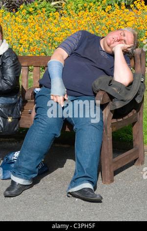 London, Westminster, Victoria Embankment Gardens große Fat junger Mann in Jeans und arm in Gips schläft oder Sonnenbaden - Stockfoto