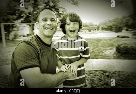 Vater und Sohn Spaß Lachen lustig unterwegs Runde Spinnen in Spielplatz im freien - Stockfoto