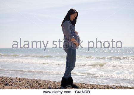 Eine schwangere Frau stehen am Strand - Stockfoto