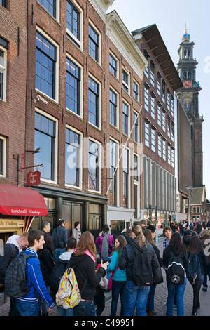 Touristen vor dem Ann Frank House am Prinsengracht mit Turm der Westerkerk (Westertoren) hinter, Amsterdam, Niederlande - Stockfoto