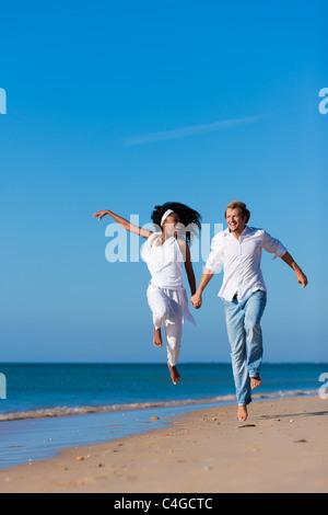 Paar - schwarze Frau und kaukasischen Mann - springen in ihren Urlaub am Strand spazierengehen - Stockfoto