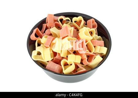 Rohe bunte Nudeln in Form von Herzen in schwarz Schüssel isoliert auf weißem Hintergrund - Stockfoto