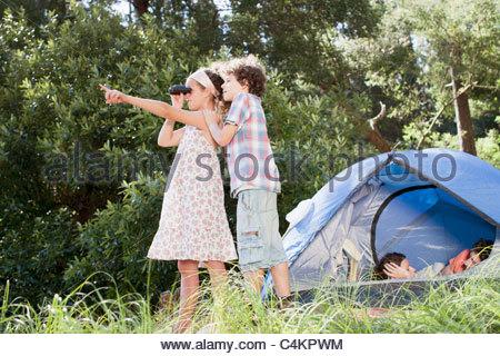 Kinder mit Fernglas und Eltern Verlegung im Zelt - Stockfoto