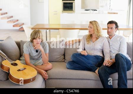 Paar auf der Suche auf ihren Sohn sitzt neben einer Gitarre - Stockfoto