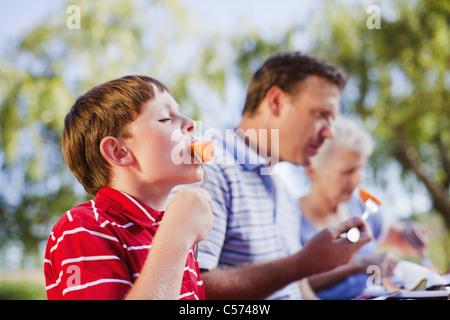 Junge Essen Melone an Picknick-Tisch - Stockfoto