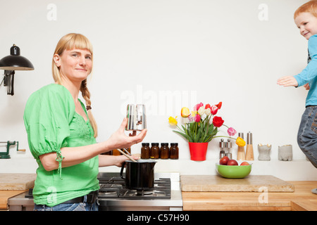 Frau, die das Kochen als Sohn spielt in der Küche - Stockfoto