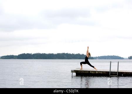 Mitte Abstand Seitenansicht einer Frau in Ashtanga-Pose am ruhigen See - Stockfoto