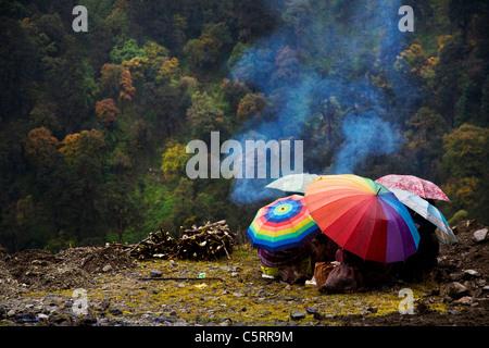 Straßenarbeiter Zuflucht unter ihren Sonnenschirmen wie es nieselt. Tawang, Arunachal Pradesh. Indien - Stockfoto