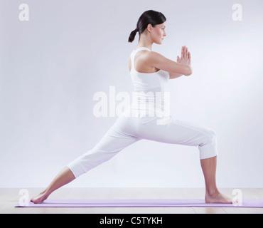 Mitte Erwachsene Frau beim Yoga vor weißem Hintergrund - Stockfoto