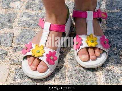 Nahaufnahme von ein paar Sandalen, dekoriert mit rosa und gelben Blüten, die von einem jungen Mädchen getragen - Stockfoto