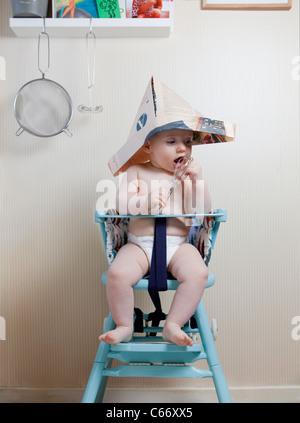 6 Monate altes Baby in Babystuhl einen Zeitung Hut sitzt - Stockfoto