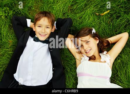 Porträt von lächelnden Kinder Braut und Bräutigam auf dem grünen Rasen liegen und Blick in die Kamera - Stockfoto