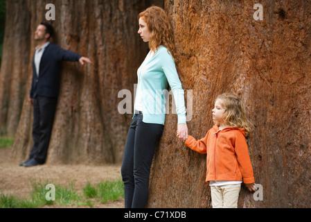 Mutter und Tochter lehnte sich gegen Baum, Vater steht trennen im Hintergrund - Stockfoto