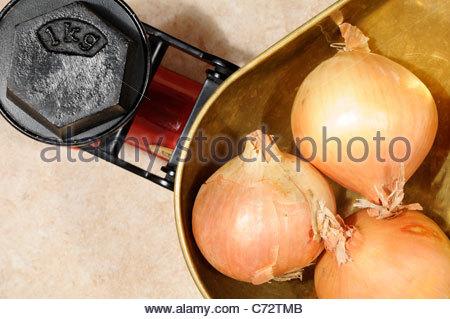 Top down Sicht auf ein 1kg Gewicht mit Zwiebeln auf altmodische Küchenwaage, England - Stockfoto