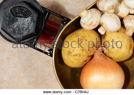 Top down Sicht auf ein 1kg Gewicht mit Kartoffeln, Pilze und eine Zwiebel auf altmodische Küchenwaage, England - Stockfoto