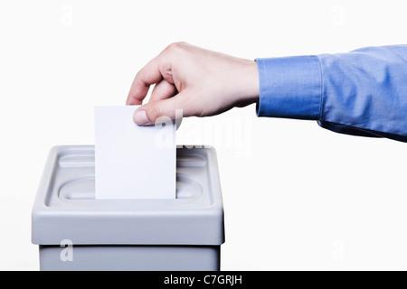 Ein Mann, einen leere weiße Stimmzettel in eine Wahlurne, close-up Hände - Stockfoto