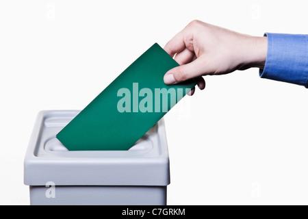 Ein Mann, einen leere grüne Stimmzettel in eine Wahlurne, close-up Hände - Stockfoto