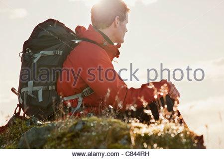 Wanderer auf grasbewachsenen Felsen sitzen - Stockfoto