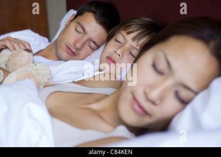Eltern und seinem kleinen Sohn zusammen im Bett schlafen - Stockfoto