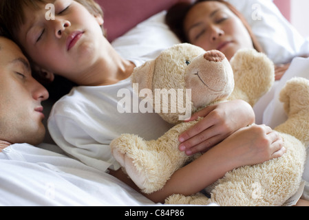 Jungen schlafen im Bett mit seinen Eltern, mit Teddy Bär - Stockfoto