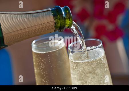 Schließen Sie Blick auf Gießen gekühlte Gläser Champagner auf sonnenbeschienenen Terrasse mit Bougainvillea Blumen - Stockfoto