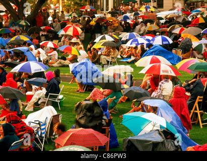 Familienspaß am Konzert im Freien sitzen unter bunten Sonnenschirmen am Stadtplatz in einem Vorort von Auckland - Stockfoto