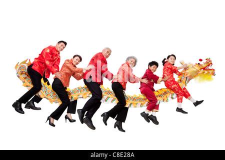 Familie gekleidet in traditioneller Kleidung Reiten ein Chinese New Year-Drache - Stockfoto