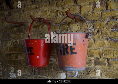 Alten Feuer Eimer hängen von Heringen an den Wänden bei Landguard Fort, Felixstowe, Suffolk - Stockfoto