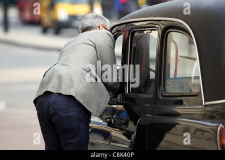 Ein Mann im Gespräch mit einem Taxifahrer in London - Stockfoto