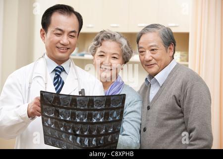Arzt zeigt ein Röntgenbild Testergebnisse, älteres paar - Stockfoto