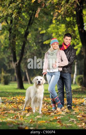 Ein Lächeln auf den Lippen Ehepaar und ihr Hund posiert im Park im Herbst - Stockfoto