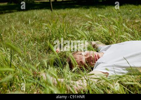 Teenager, die Verlegung in hohe Gräser - Stockfoto
