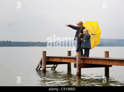 Kinder mit gelben Regenschirm auf dock - Stockfoto