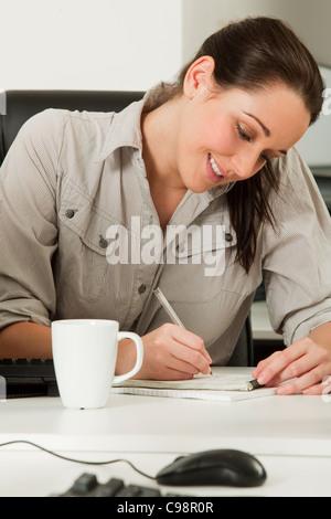Weibliche Büro Arbeiter schreiben notebook - Stockfoto