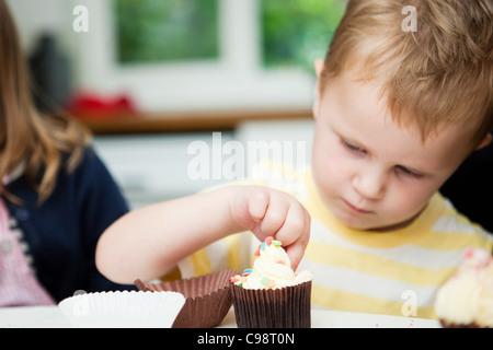 Kleiner Junge Muffins dekorieren - Stockfoto